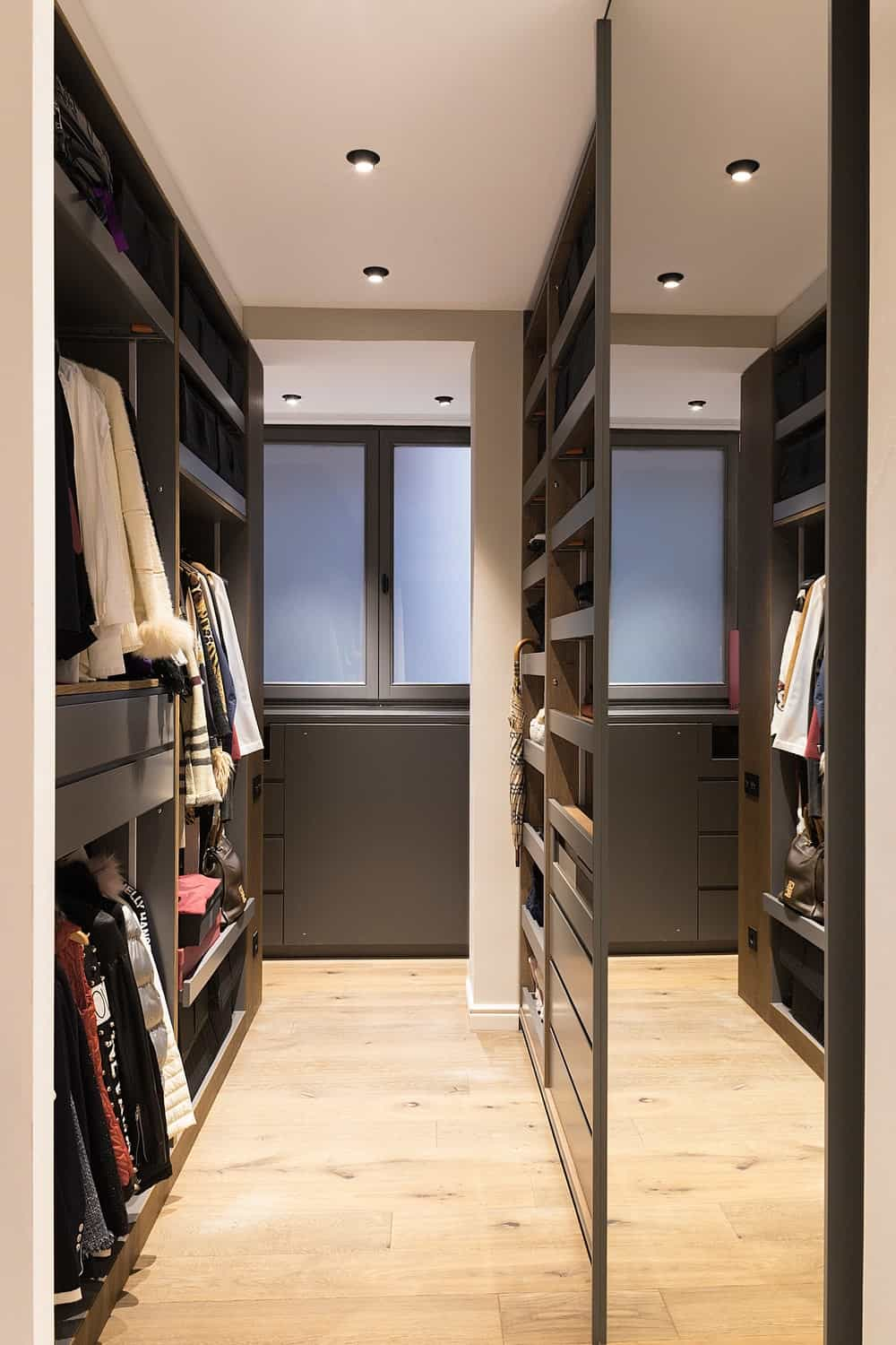 This is the walk-in closet of the bedroom with large structures on either side filled with shelves, cabinets and racks.