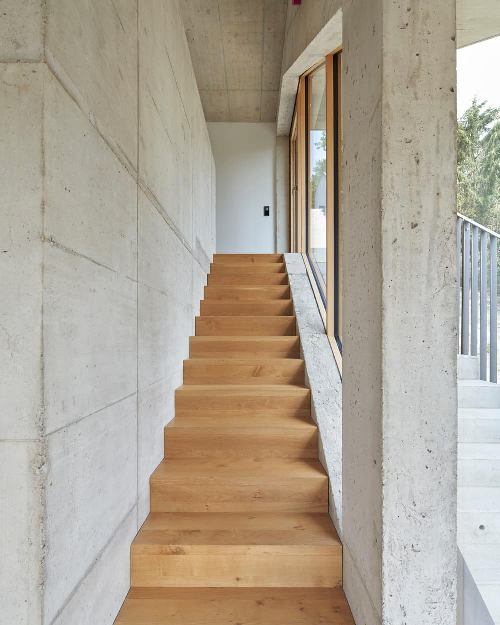 This is a view of the interior staircase with wood toned steps to match the hardwood flooring brightened by the glass walls.