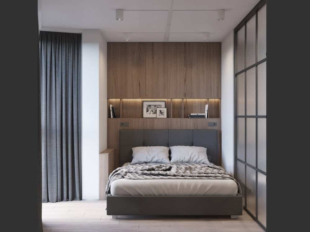 This is the bedroom on the otehr side of the opaque glass wall of the living room. It has a large gray bed that matches the gray curtain.