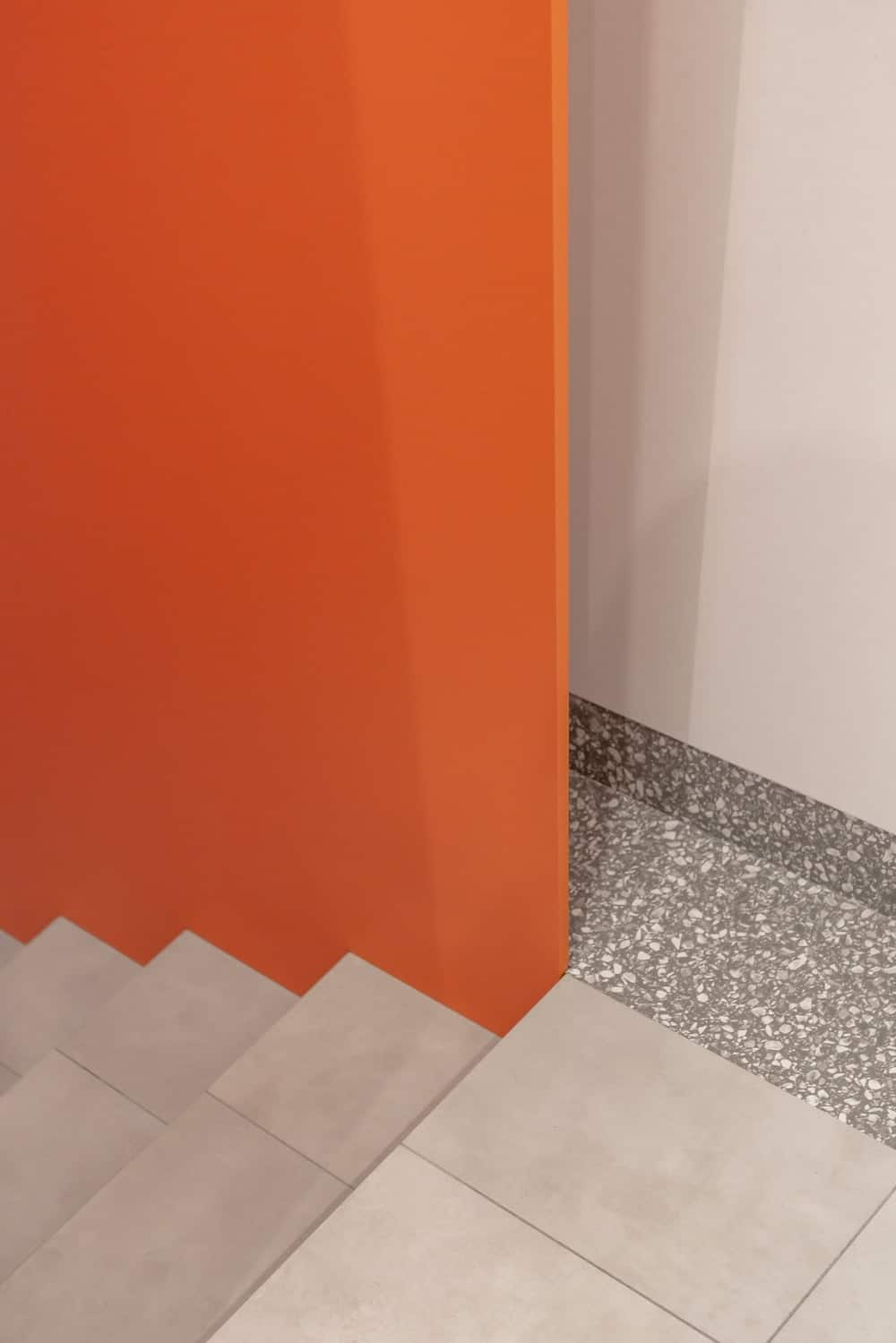 This is another view of the staircase with its light gray steps and floor contrasted by the bright orange wall on the side.