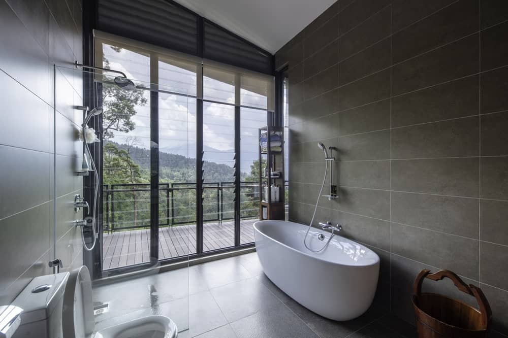 This bathroom has a large white porcelain bathtub that stands out against the gray tiles of the floor and wall.