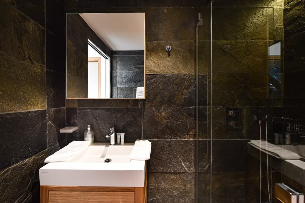 The small vanity stands out in this bathroom against the surrounding consistent dark marble tiles.