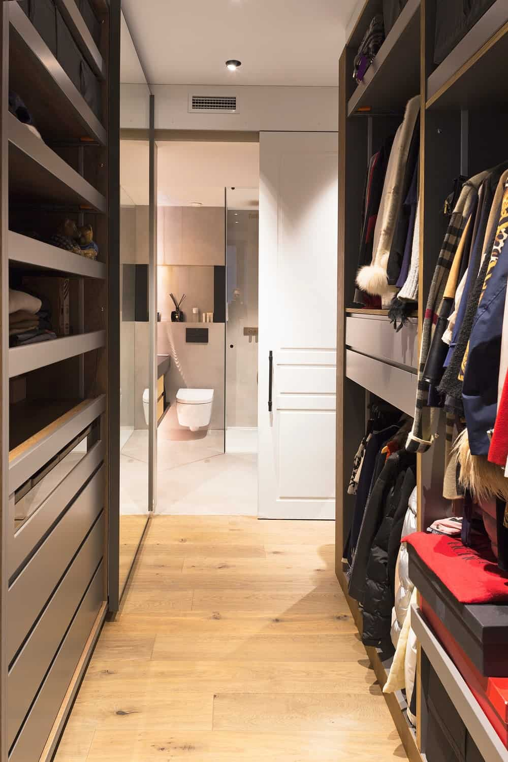 At the edge of this walk-in closet is the access to the bathroom.