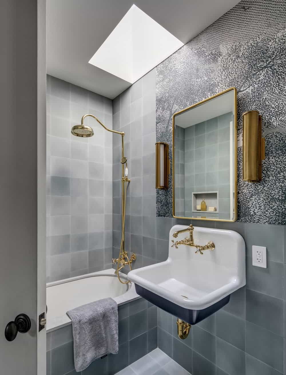 The bathroom has consistent gray tiles on its walls that make the bronze fixtures and white porcelain sink and tub stand out.