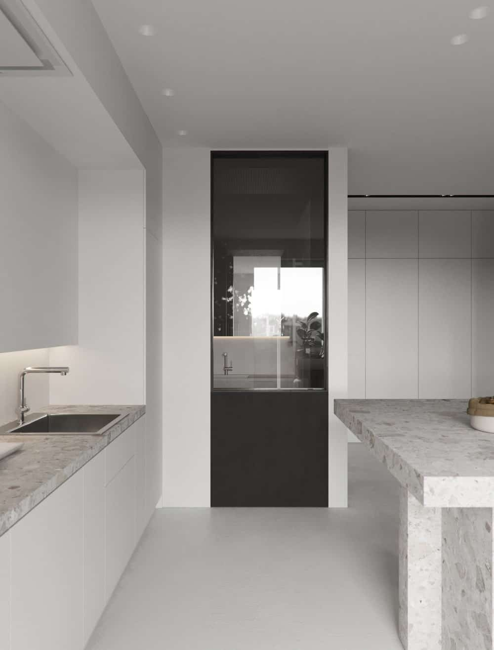 The dark window that leads to the bathroom stands out in the white kitchen. This has a glass panel that shows a glimpse of the bathroom vanity.