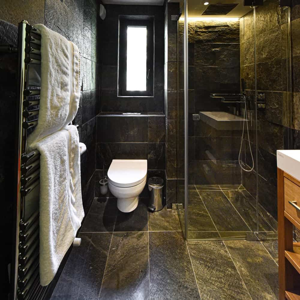 This other bathroom has dark marble tiles on its walls and floor making the toilet stand out placed by the glass-enclosed shower area.