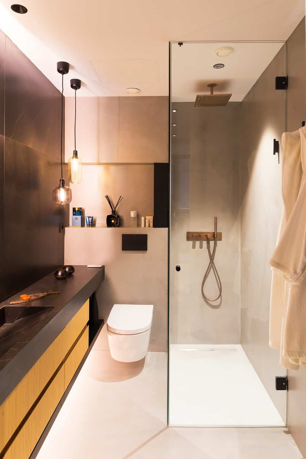 This is a close look at the small bathroom with a dark vanity, a floating toilet and a glass-enclosed shower area.