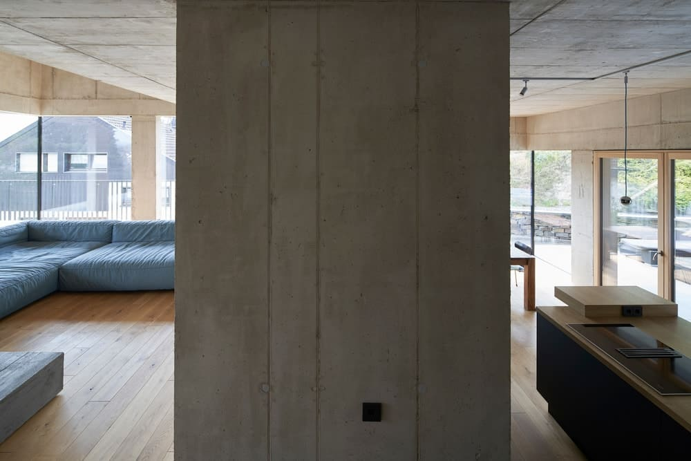 There is a thick wall of concrete separating the living room area and the kitchen and dining area.