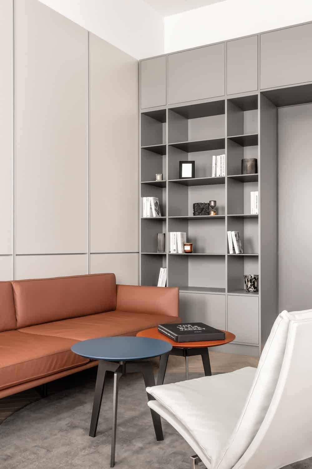 At the far end of the room is a couple of built-in shelves that are used for books and decors flanking the door of the room.