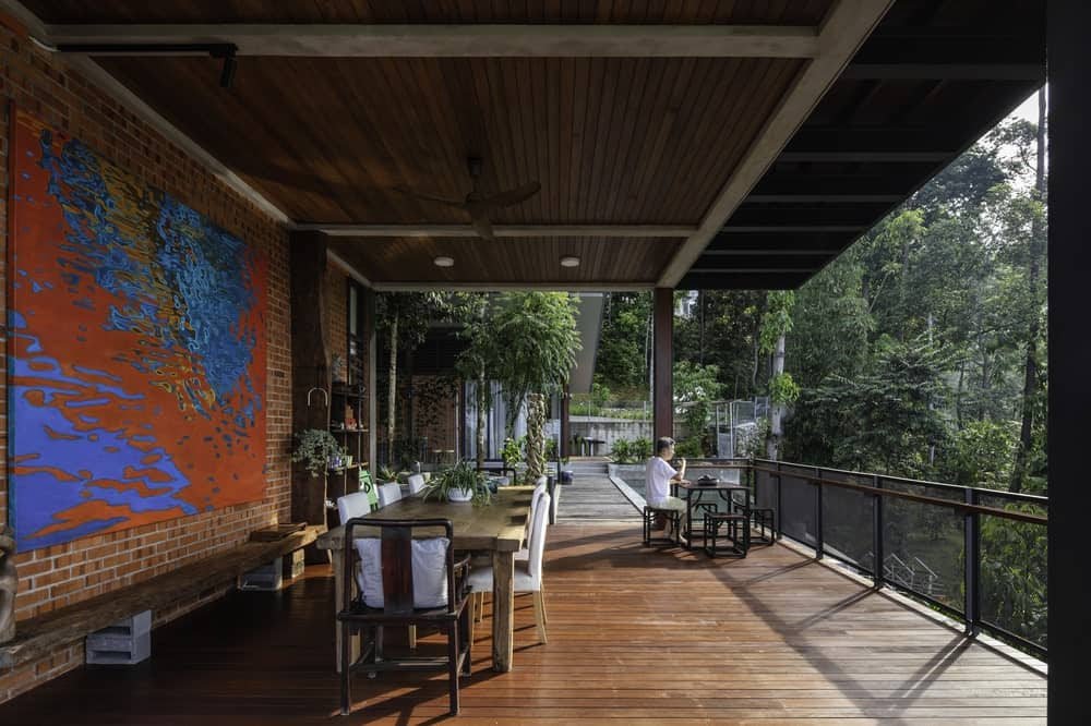 This is a large covered balcony with an outdoor dining area and a breakfast nook at the far corner by the glass railings.
