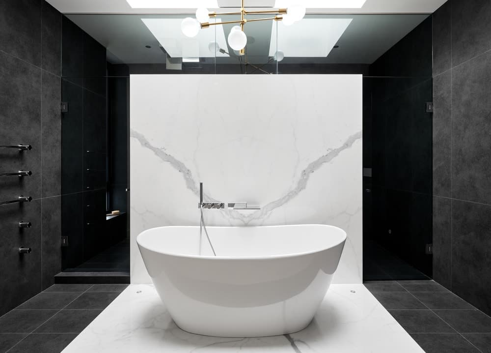 This is a close look at the freestanding bathtub adorned by its white marble wall that also acts as barrier for the shower area behind it.