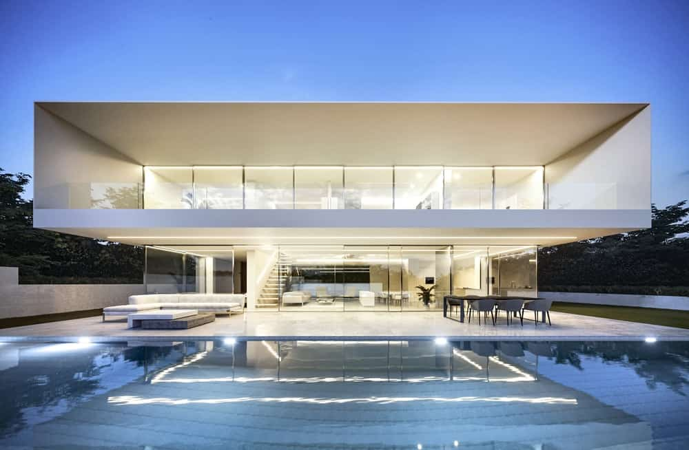 This is a view of the back of the house with the two levels glowing with warm lights showing the glass walls and the interiors of the house.