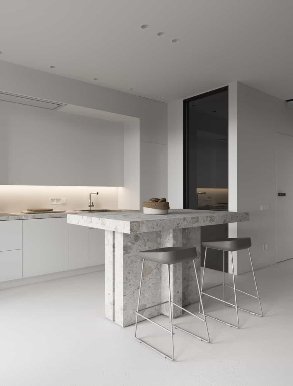 The small gray marble kitchen island is complemented by a couple of gray stools.