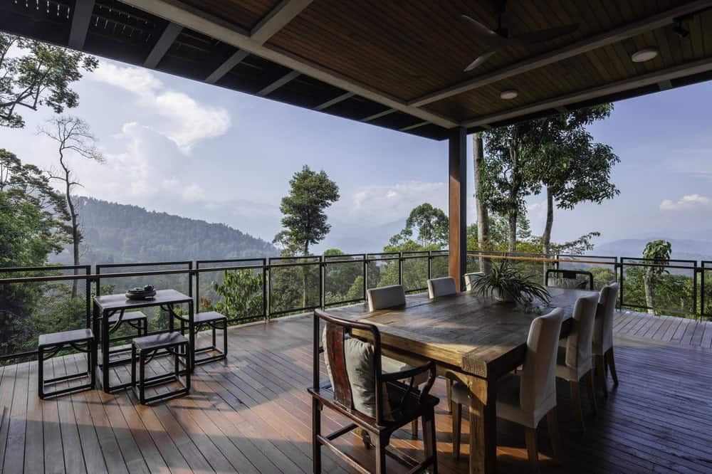 This large balcony with the outdoor dining sets has a sweeping view of the surrounding landscape topped with a wooden ceiling.
