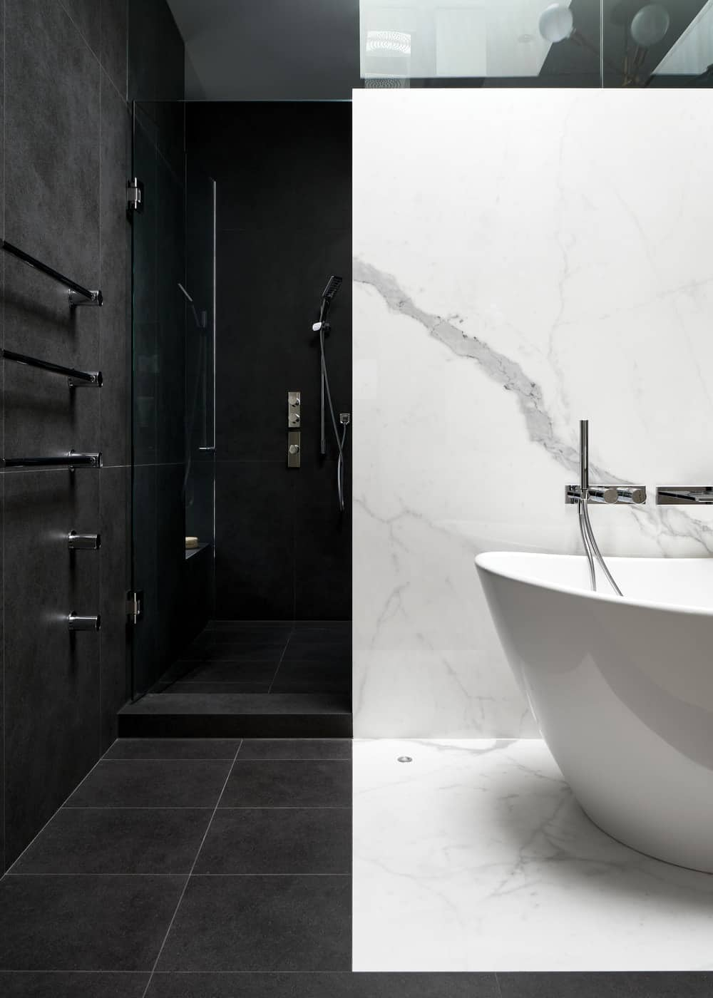 This is a close look at the walk-in shower area behind the bathtub wall with dark gray tiles on its walls and floor.