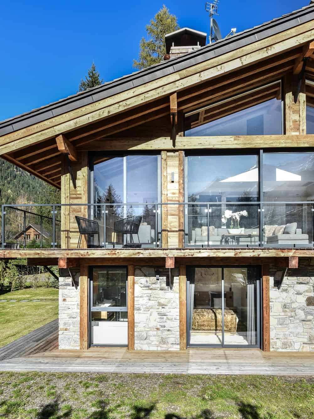 This side of the house showcases the second level glass walls and the ground level stone walls that also has glass walls and doors.