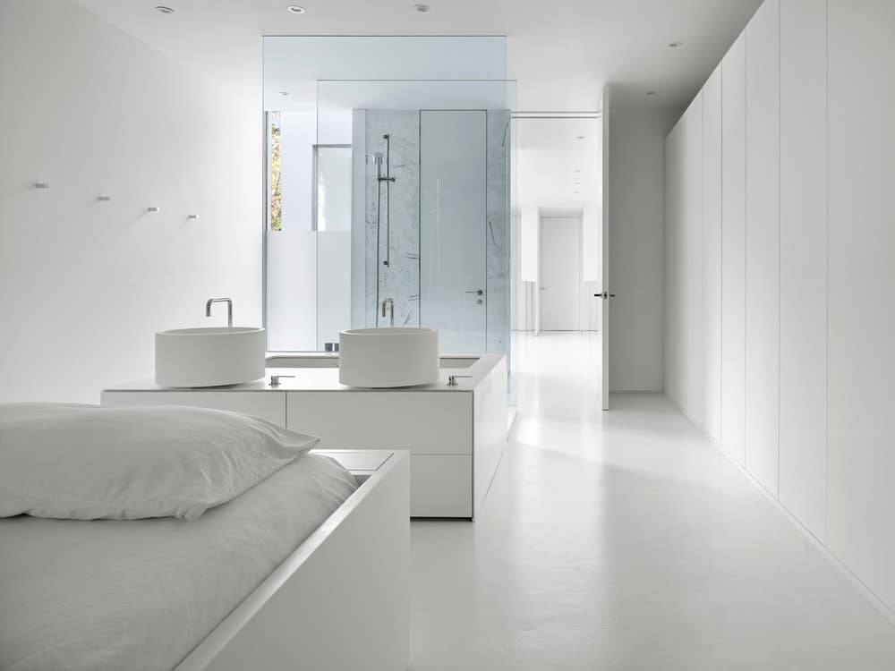 This is a look at the bathroom from the vantage of the white modern bed that matches well with the floor, walls and ceiling.