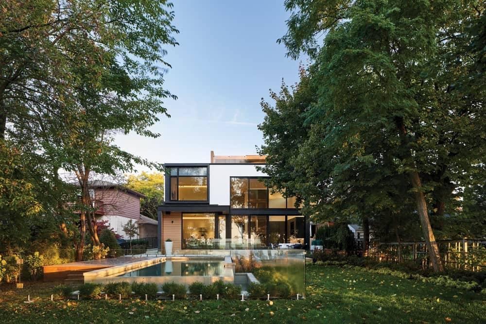 This is a view of the house from the vantage of the large backyard lawn of grass shaded by tall trees that also provide privacy for the pool and the glass walls of the house.