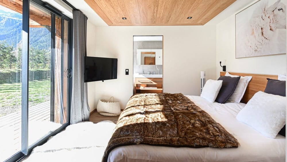 This is the bedroom with a large bed across from the glass wall with a wall-mounted TV on the side.