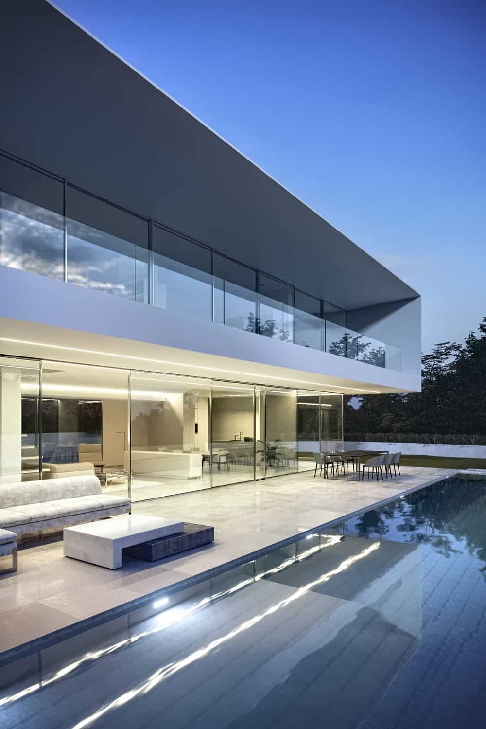 This shows the backyard pool with the patio lights on giving a warm view of the ground level interiors through glass walls.