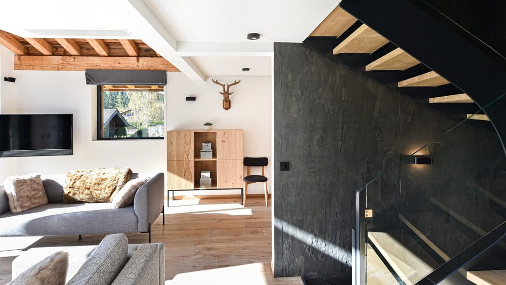 A few steps from the living room is the staircase that has wooden steps that stands out against the dark gray walls.