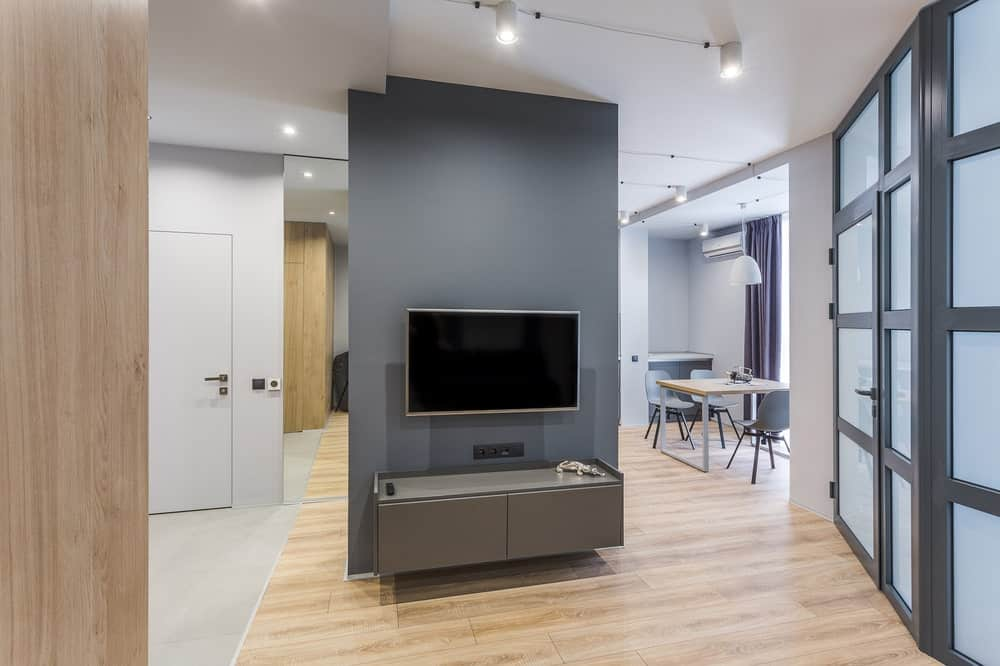 This is a look at the gray wall from the vantage of the sofa. The wall supports the wall-mounted TV and there is a view of the dining area on the right side.