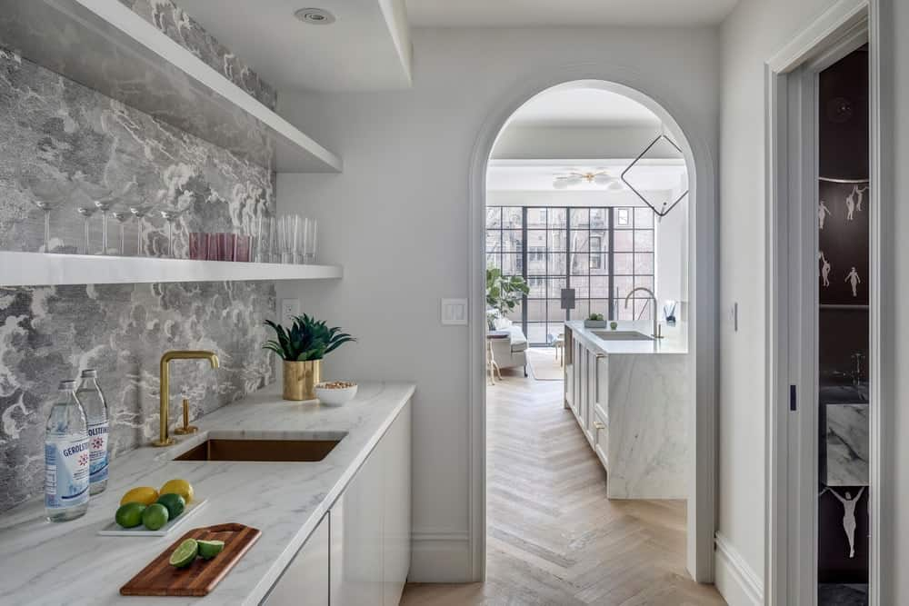 Through an arched entryway in the kitchen is the pantry area with a separate sink area and open shelves above.