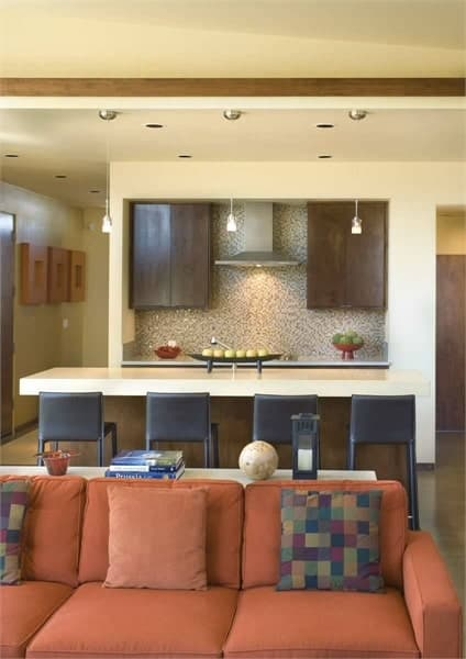 The kitchen sits behind the orange sectional. It has a large island and quartz countertops accentuated with mosaic tile backsplash.