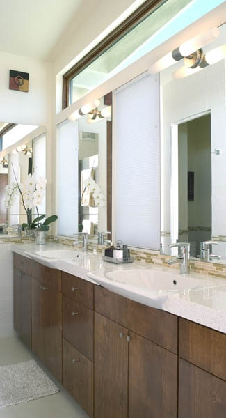 Primary bathroom with dual sink vanity and a toilet room reflected in the frameless mirrors.