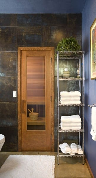 Bathroom with a metal shelving unit and a glazed wooden door that leads to the sauna room.