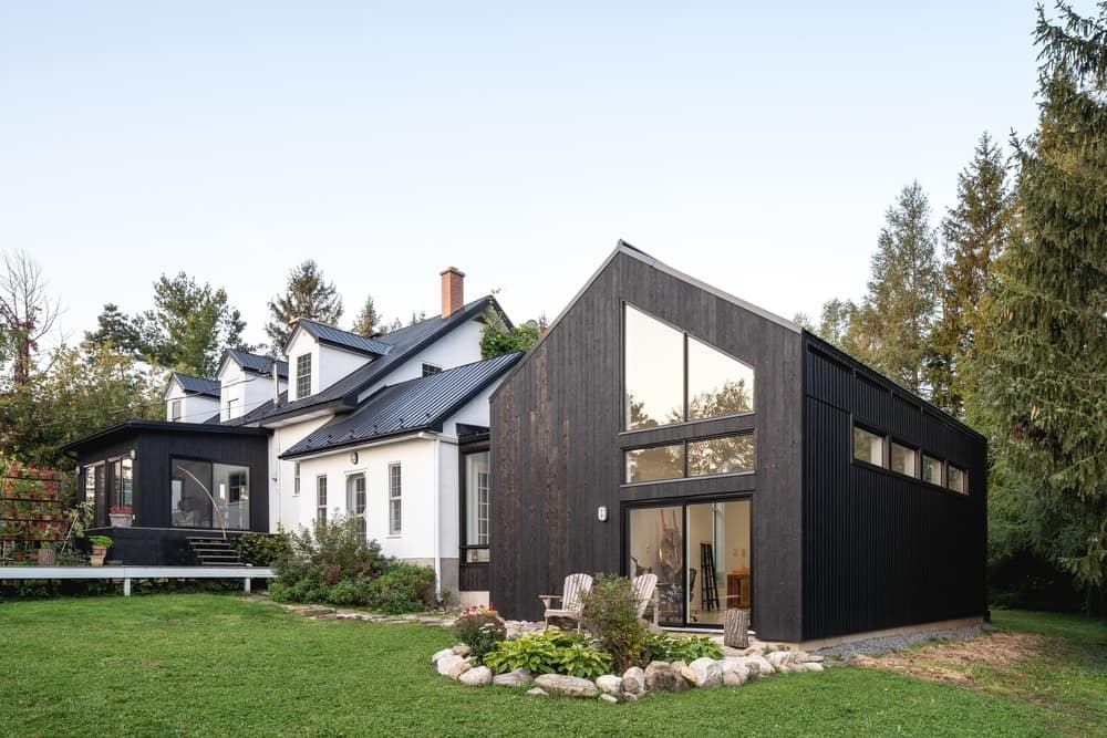 The back of the house shows more of the simple and modern designs of the extension structure in contrast with the more traditional look and light tones of the main house.