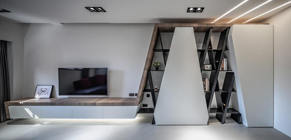 This is the wall of the living room across from the sectional sofa. with a unique design to its built-in shelves and entertainment floating cabinet beneath the wall-mounted TV.