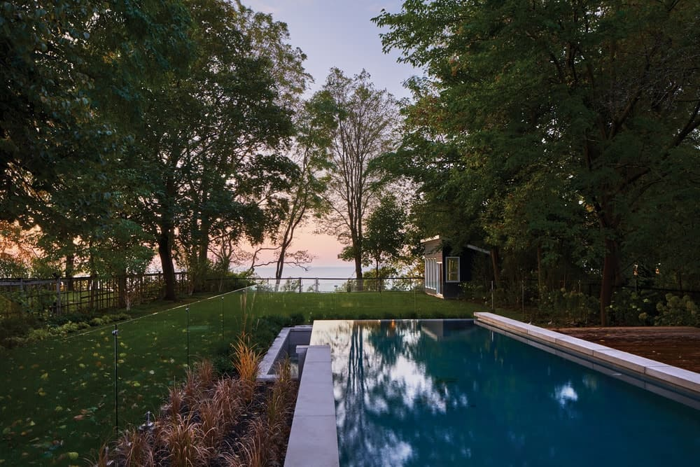 This is a view of the landscaping applied to the backyard of the house with a lush grass lawns, tall trees and flowering shrubs that bring color to the poolside area.