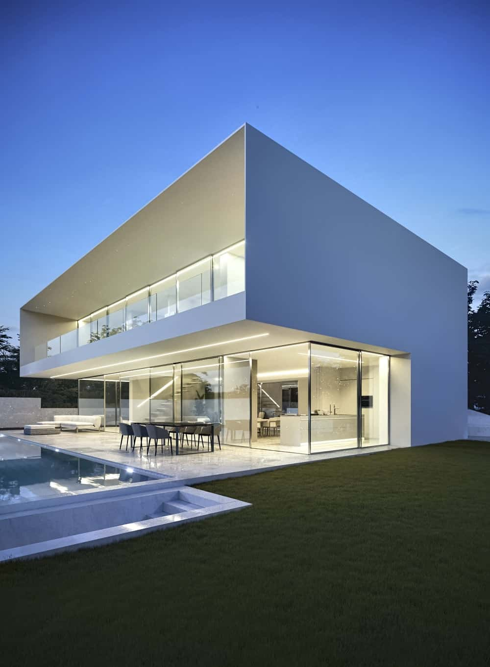 This is a view of the house showcasing the covered patio and the large balcony with glass railings and both levels are lit.