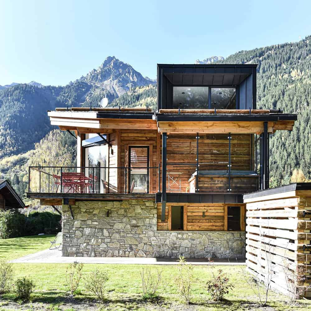 This is a view of the side of the house that has three distinct materials to its exteriors namely stone, wood and metal complemented by the glass walls.