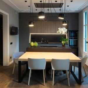 The dark kitchen island has an extension of wooden dining table paired with modern dining chairs topped iwth modern pendant lights.