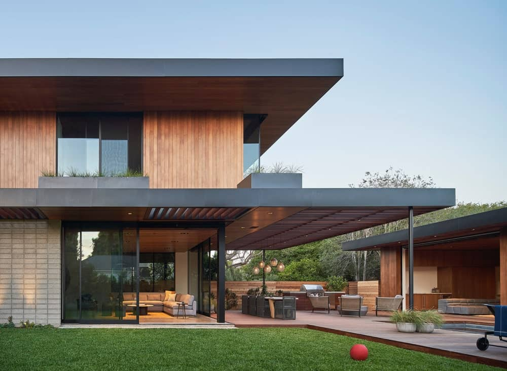 This isde of the house also has a grass lawn that gives a nice contrast to the glass walls and wooden exteriors.
