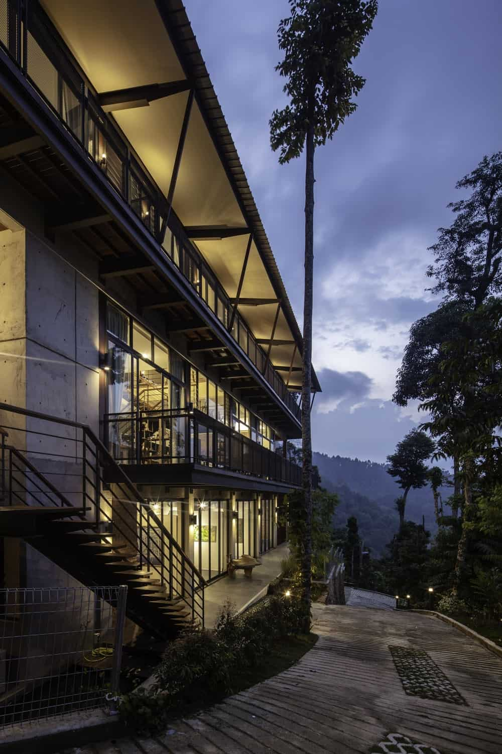 This nighttime view of the house shows the balconies that glow warmly from the interior lights that escape through.