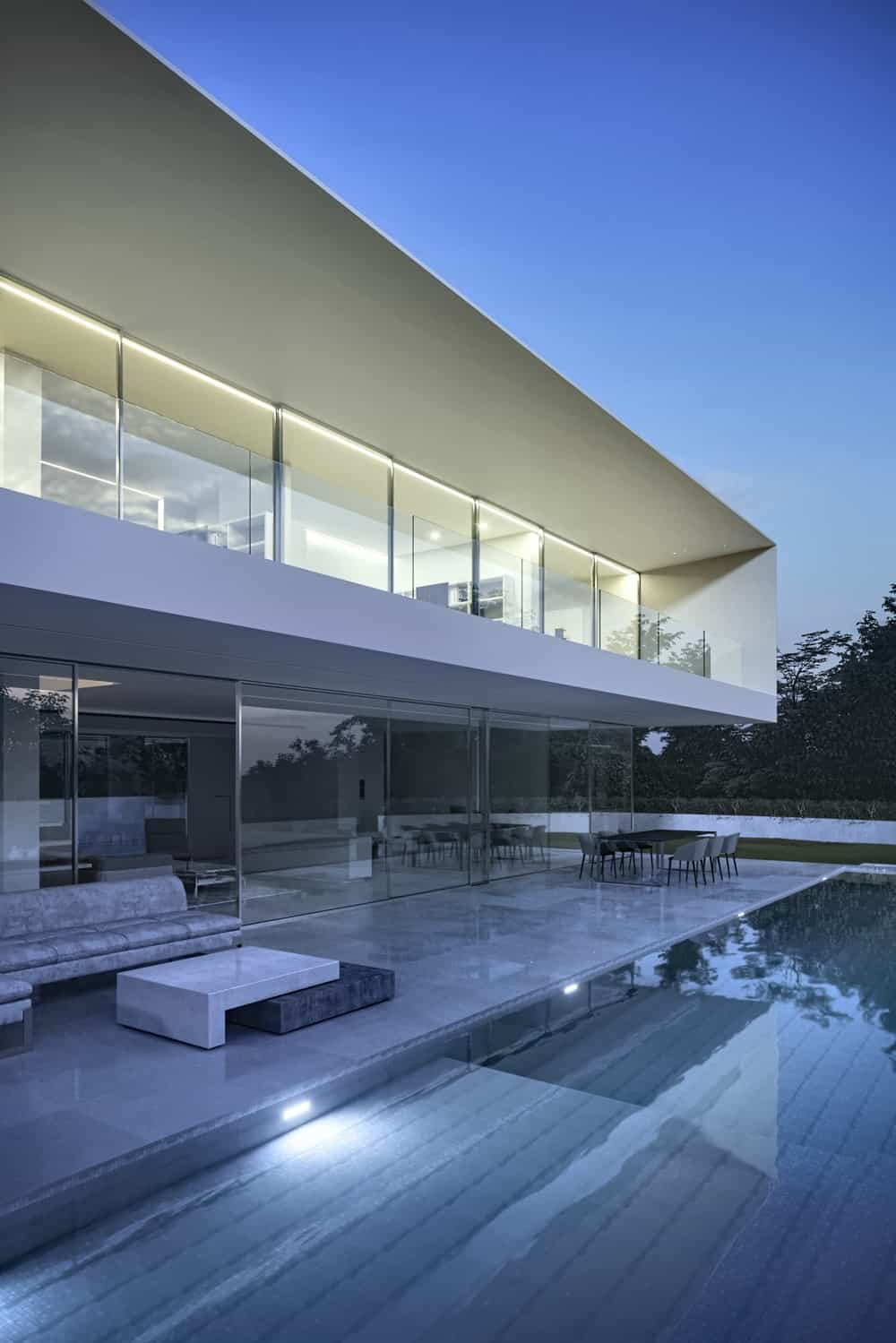 This is a view of the back of the house with a large infinity pool lined with white marble walkways that match the white tones of the house exterior.