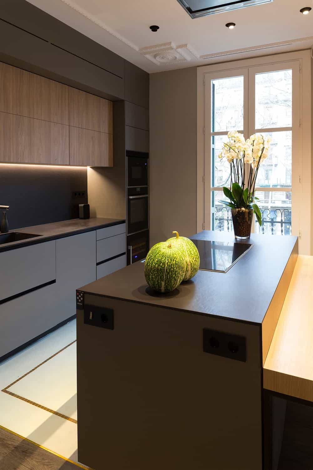 This is a close look at the modern kitchen that has matte cabinetry that goes well with the dark modern appliances embedded into the cabinetry and island.