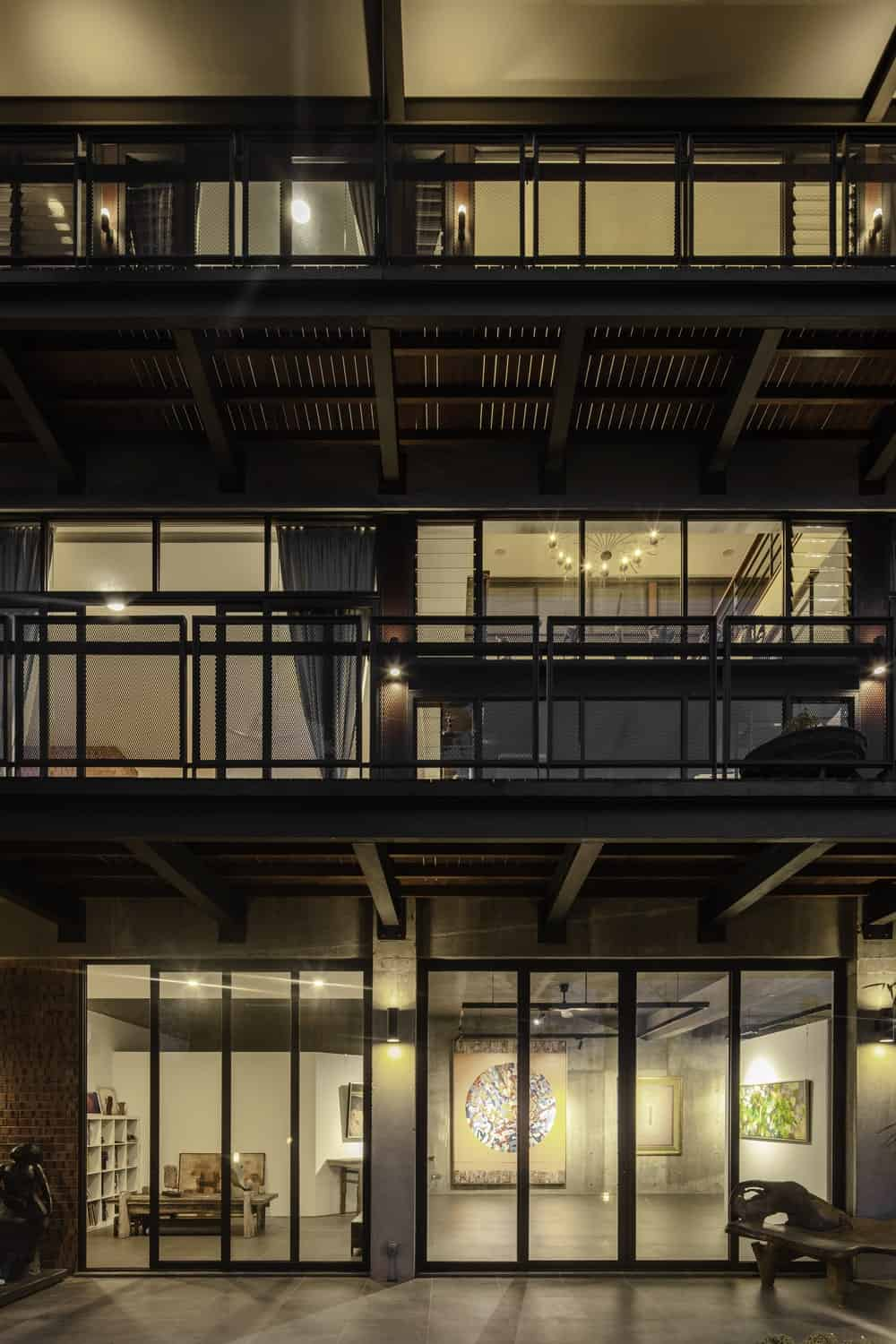 This nighttime view of the house glass walls showcases its warm glow that comes from the interior lights.