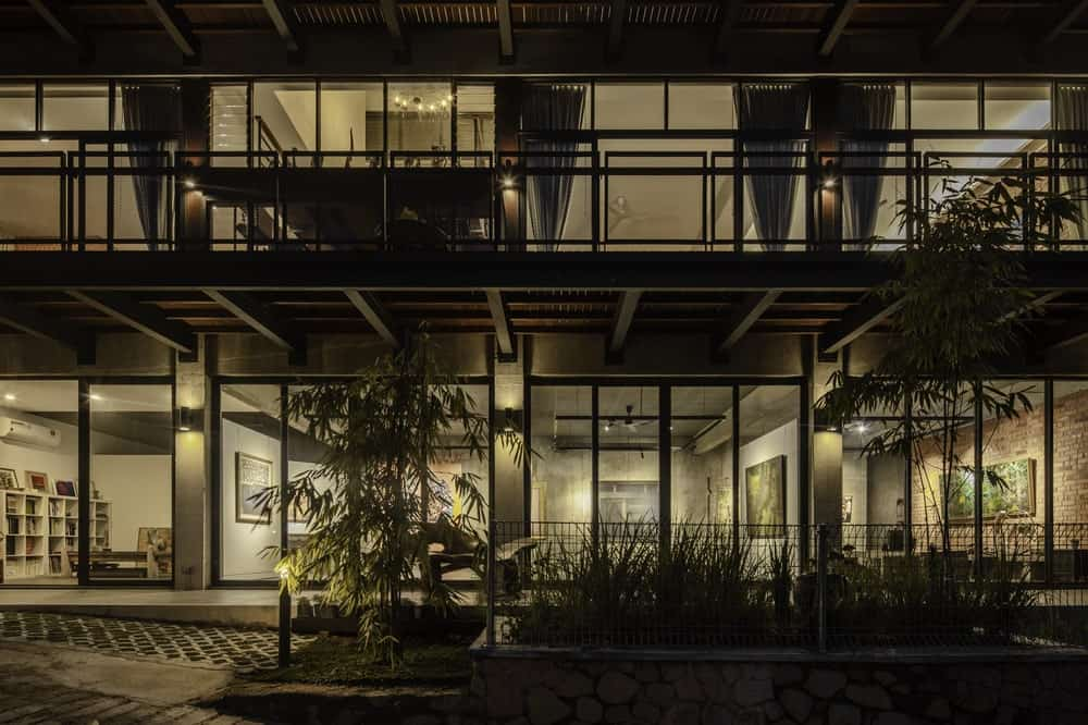 This view of the house shows the abundance of glass walls on the two levels of the house that glows warmly.