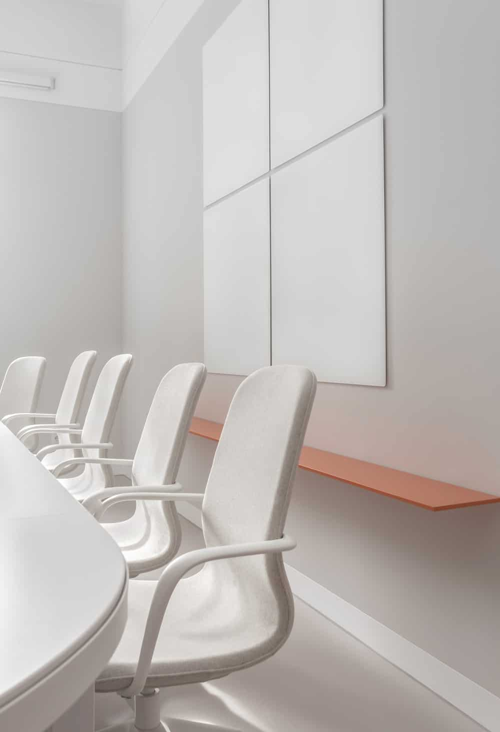 On the other side of the conference table is a floating orange shelf topped with a set of wall decoration.