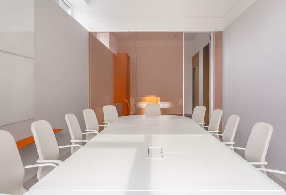 This is a close look at the white conference table with a sleek finish surrounded by white office chairs.