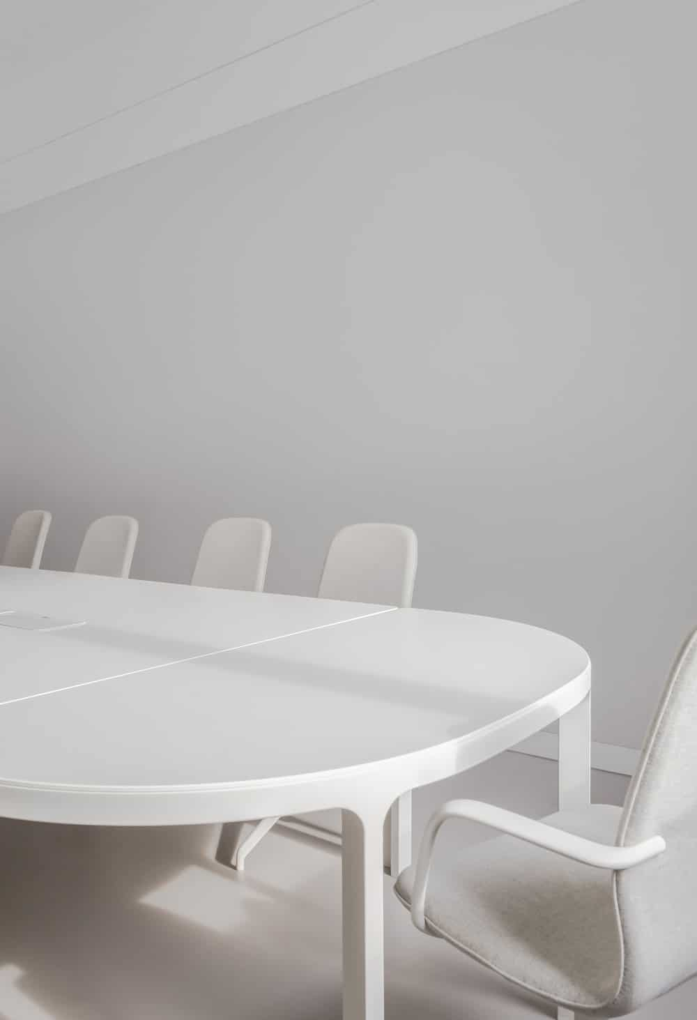 This is a close look at the modern conference table that pairs perfectly with the white office chairs, white walls and white ceiling.