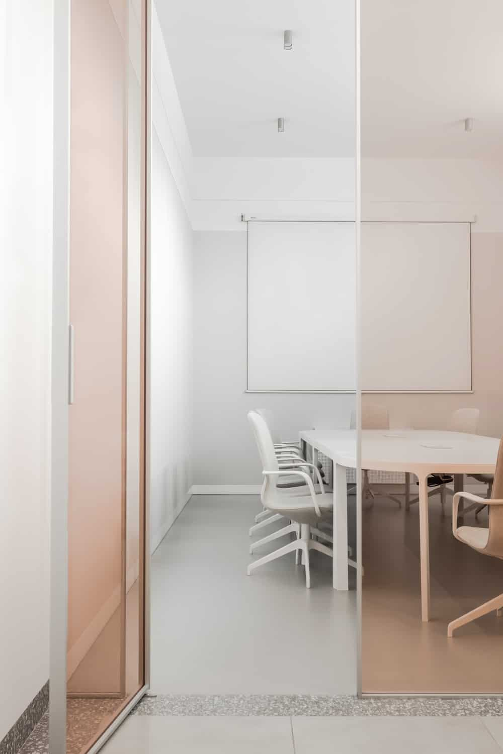 This is a closer look at the conference room with a set of white office chairs surrounding the large white conference table with a roll down projector screen at the far wall.