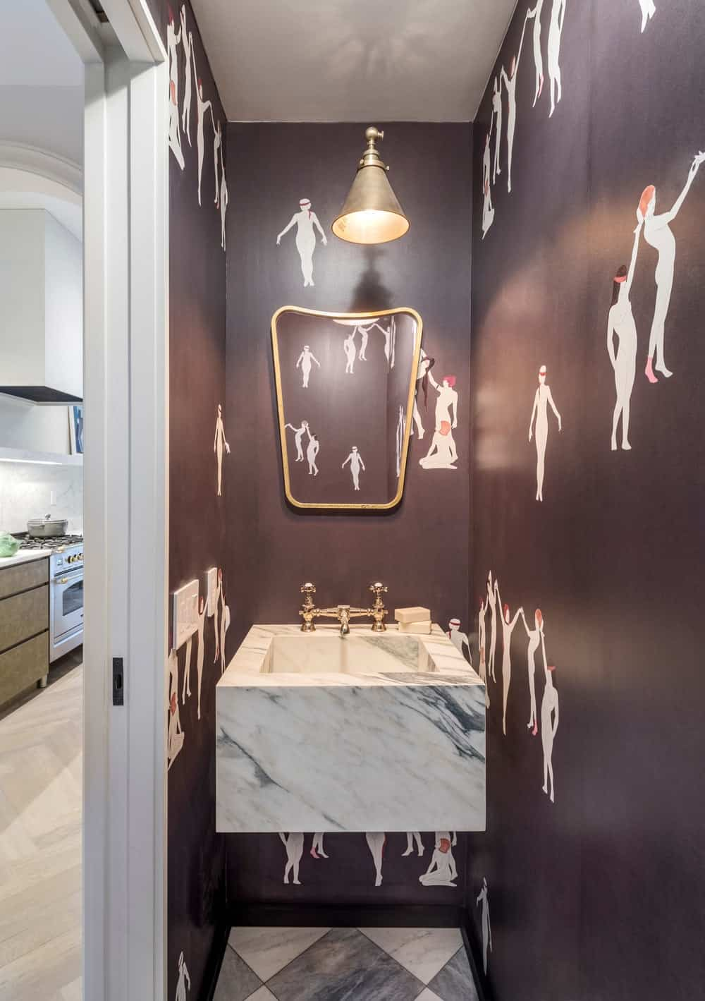 This is the small powder room with a floating white marble sink surrounded by a dark patterned wallpaper.