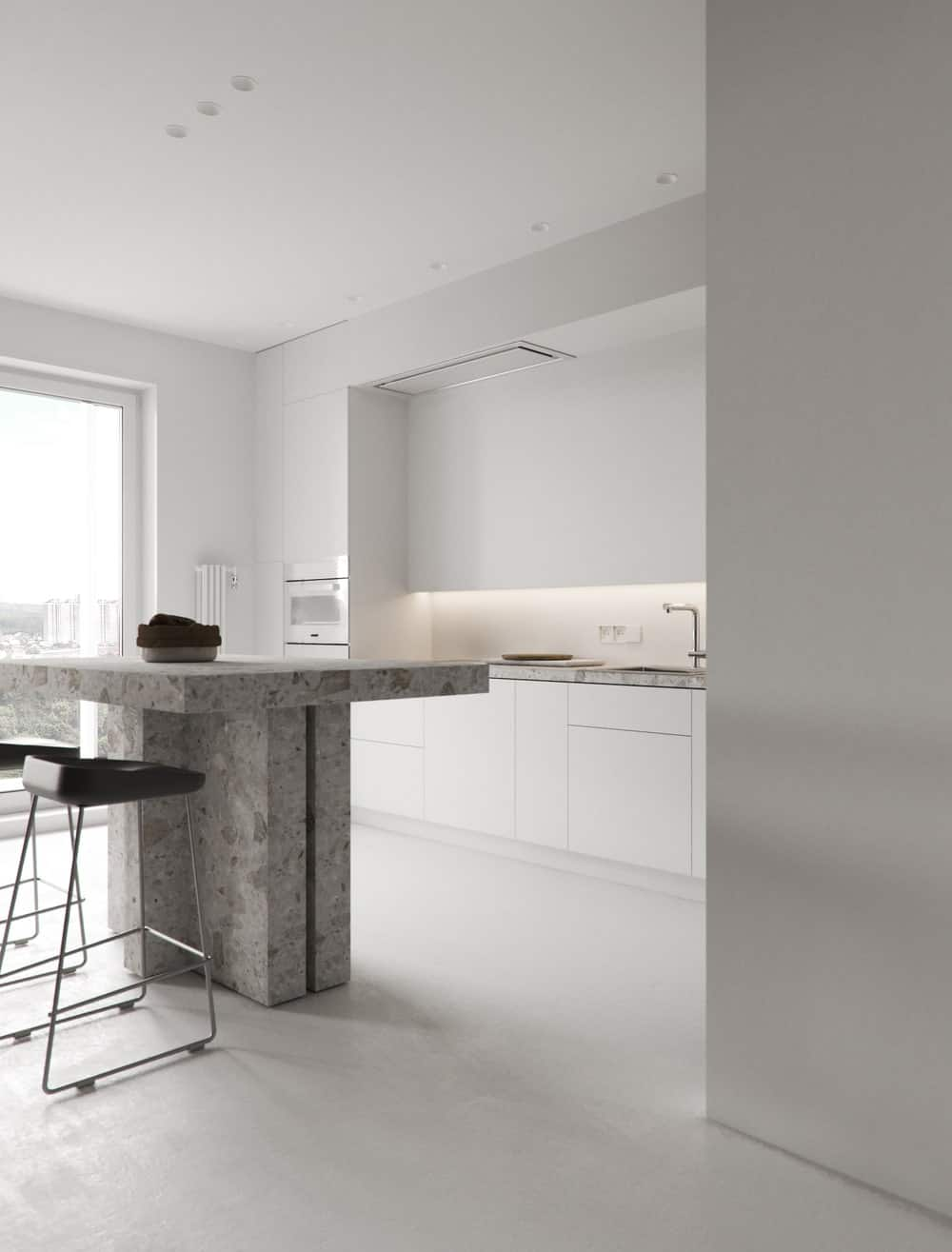 The white tones of the whole kitchen makes the gray marble kitchen island stand out.