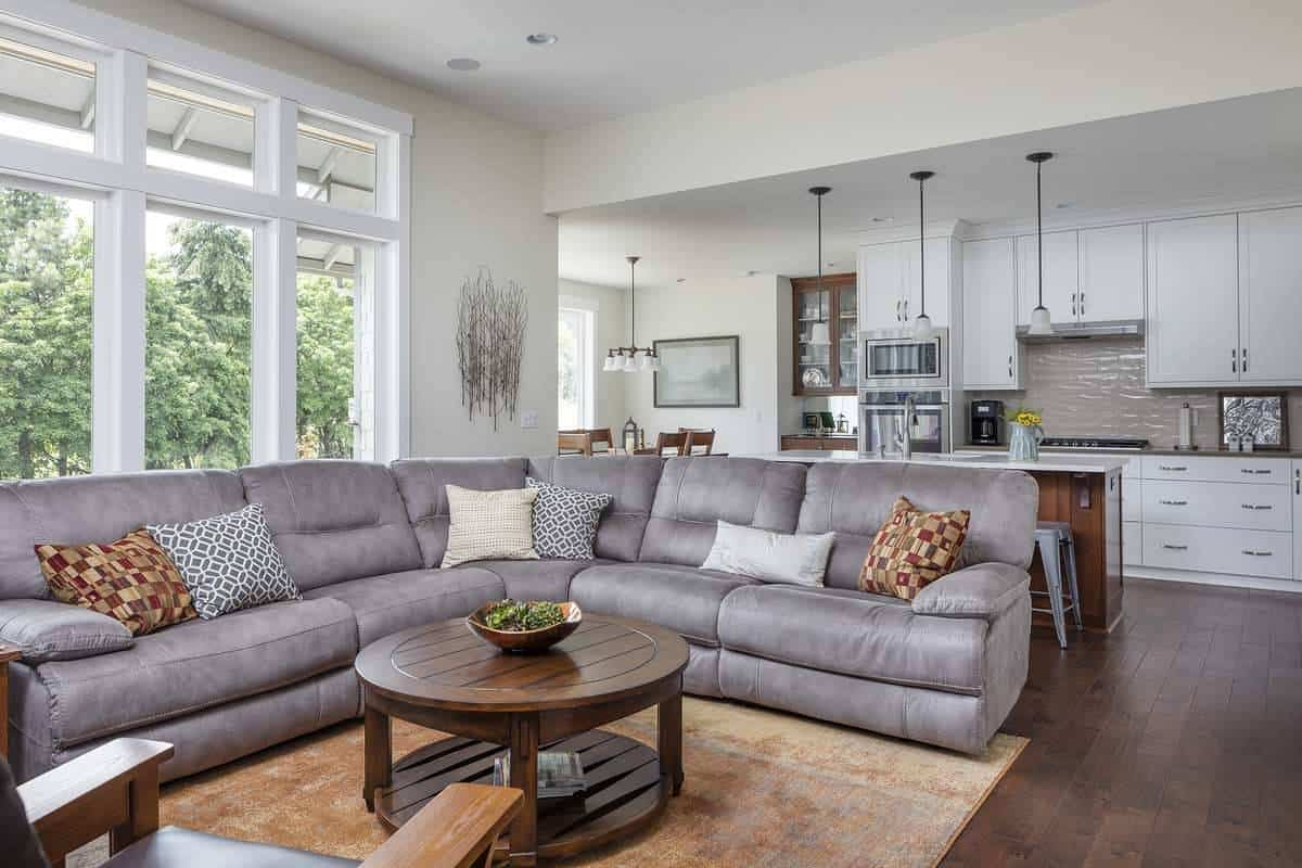 The living room has a gray V-shaped sectional, a round coffee table, and a three-panel window that invites natural light in.