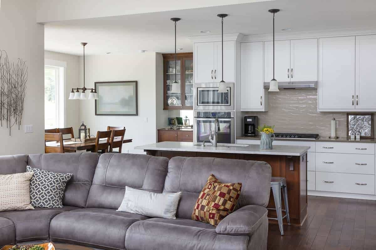 Behind the sofa is the eat-in kitchen with white cabinetry, stainless steel appliances, a center island, and a wooden dining set.
